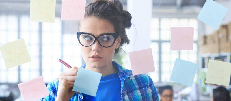Woman with glasses staring at sticky notes