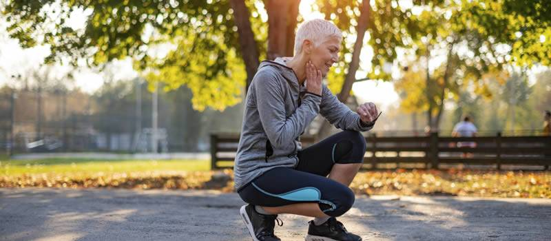 Jogger squats while checking wrist watch