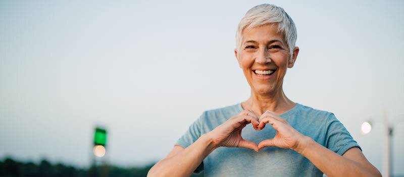 Older woman outdoors making a heart shape with hands