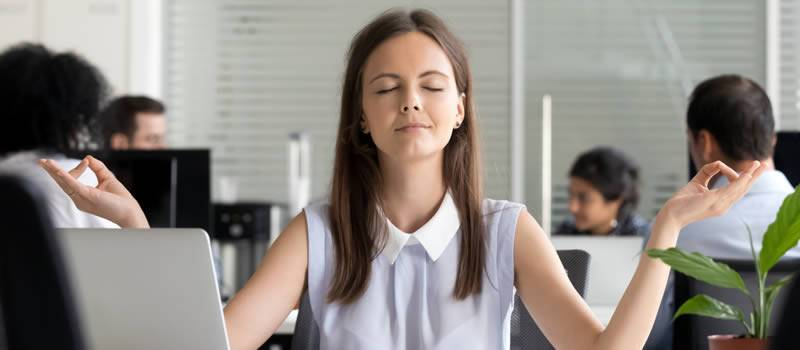 Woman meditates at her office desk