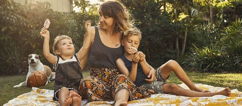 Children eat ice cream outside with mother and dog